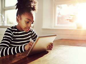Young girl sitting with tablet in hands