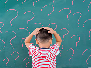 Boy, backside facing, hands on head facing wall of question marks, thinking for solution