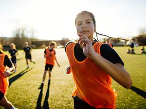 Running teenage girl soccer player